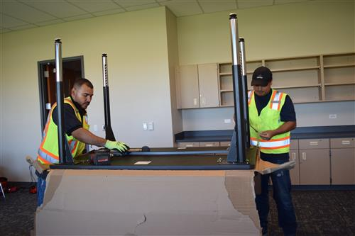 Workers are assembling furniture in classrooms.