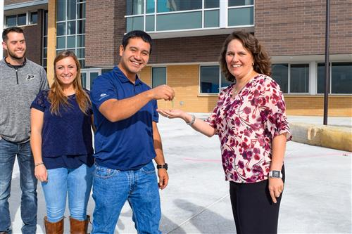 Saunders Construction team turns over the keys to the school to principal.