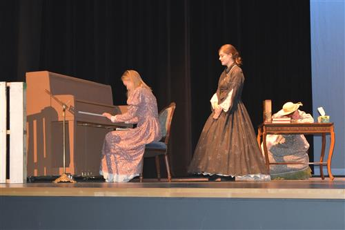 One of the sisters in Little Women is happy to receive the gift of a piano.