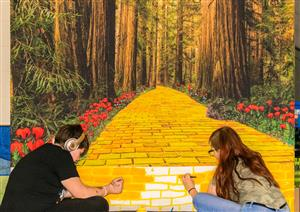 students paint a yellow brick road backdrop