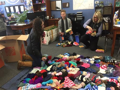 Melissa Rippy with Brighton High students putting out beanies