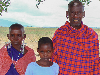 young girl poses with parents in tanzanian village