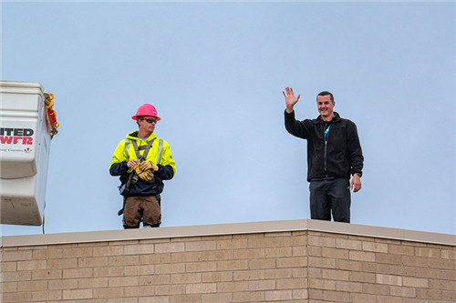 northeast principal toby karr is helped onto roof by united power employee