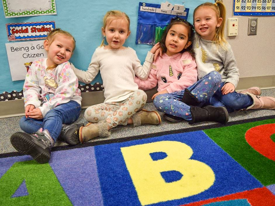 four kindergarten students sit on alphabet rug