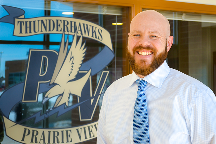 michael burke in front of prairie view high thunderhawks emblem